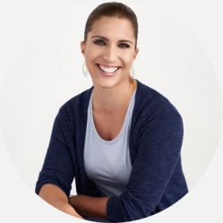 Head shot of a life coach in a blue tshirt and blue cardigan smiling at the camera
