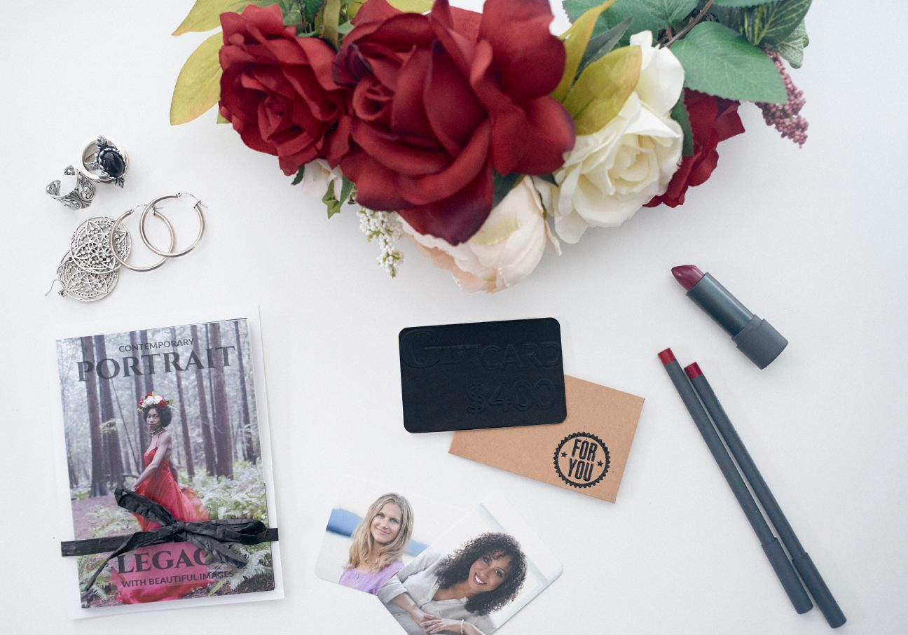 Flat lay of a flower crown, jewellery and cosmetics surrounding a gift voucher