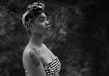 Black and white studio light portrait of a young black woman wearing a head scarf sitting in profile