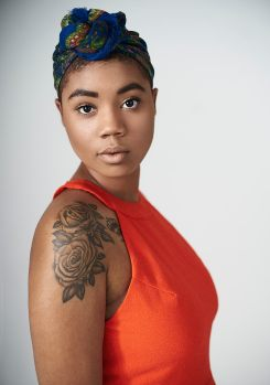Studio light portrait of a young black woman with tattoos wearing a bright orange dress and a blue patterned head scarf looking directly at the camera
