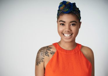 Studio light portrait of a young black woman with tattoos wearing a bright orange dress with a blue patterned head scarf smiling at the camera