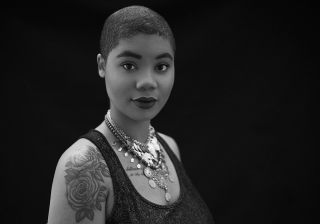 Black and white studio light portrait of a young black woman with close cropped hair wearing layered necklaces looking directly at the camera