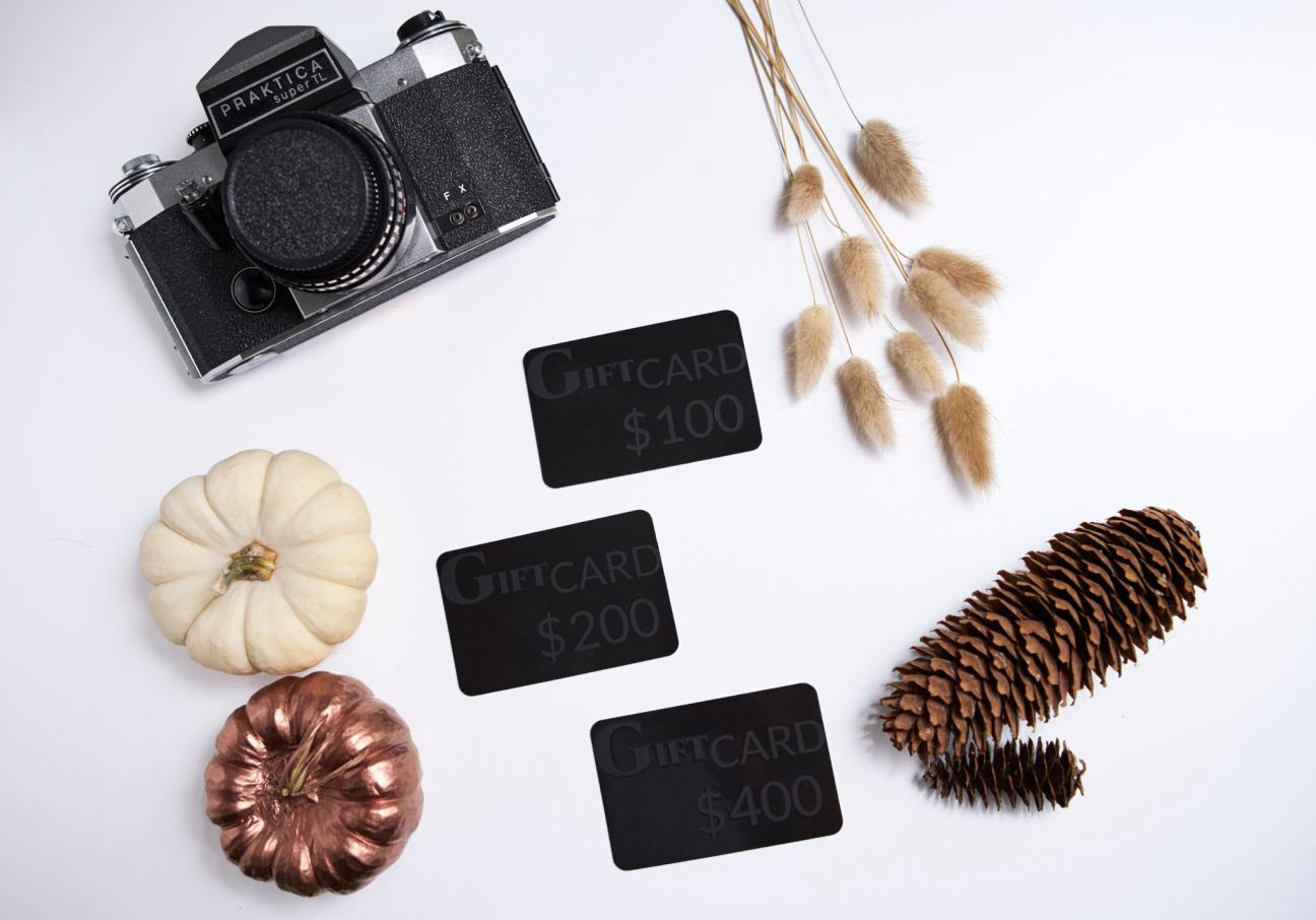 Flat lay photograph showing different denomination gift vouchers and autumn theme of pumpkins, dried grass and pine cones