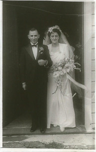 A legacy portrait of a newly married couple standing in a church doorway in 1946