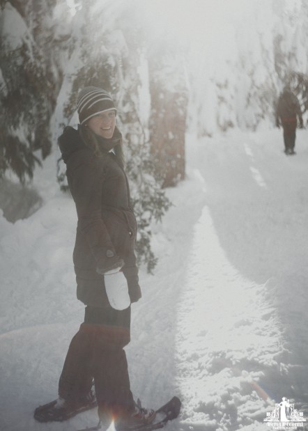 Natural light portrait of a smiling young woman snowshoeing on Cypress Mountain in Vancouver