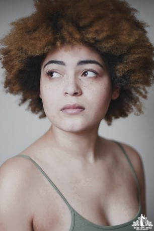 Portrait of a young woman with freckles and natural curly hair looking off camera