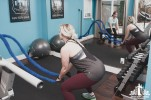 Woman using battle ropes being instructed by a personal trainer in a small gym studio
