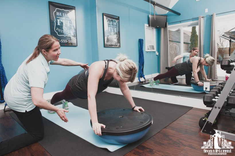 Image of a personal trainer helping a client during a session in their studio