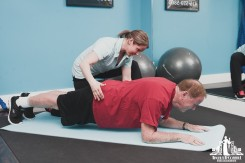 Image of a personal trainer demonstrating correct planking form during a session with an elderly client