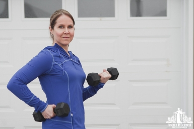 Portrait of a personal trainer using hand weights and looking at the camera