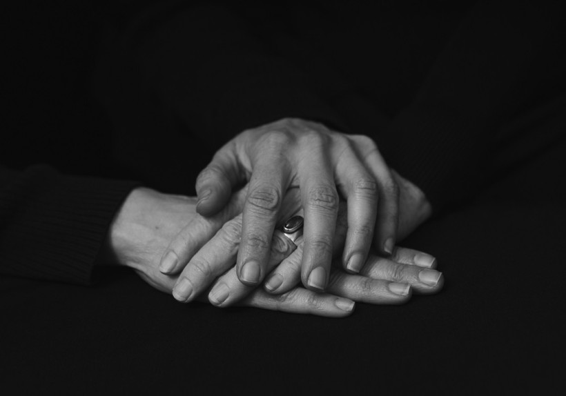 Black and white photo of a woman holding her elderly mothers hand between her own