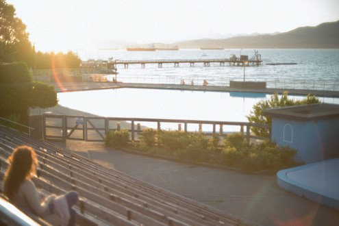 Woman watching the sunset overlooking Kitsilano pool