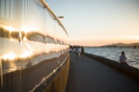 Reflection of sunset in wall of Kitsilano pool with people walking the seawall