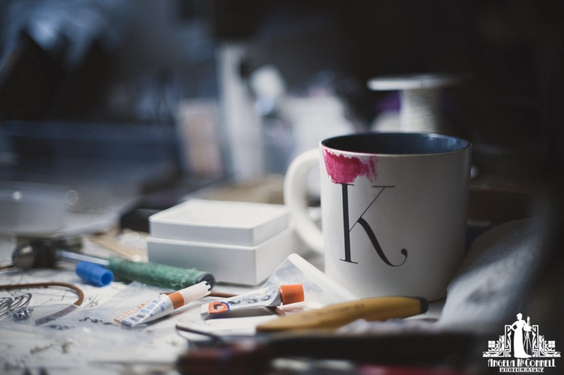 Photo of a white coffee cup with red lipstick stain on a jewellery designers desk