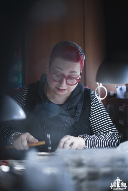 Lifestyle portrait of a jewellery designer with red hair and red eye glasses working on a design in their studio