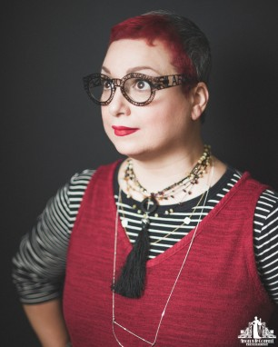 Studio head shot of a female entrepreneur with stacked necklaces, intricate eye glasses, red lips and red hair
