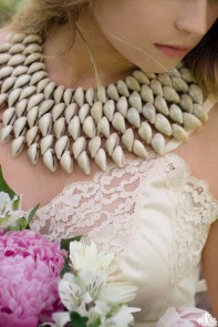 Partially obscured portrait of a young woman wearing a conch shell necklace and hold pink peonies