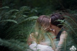 Natural light portrait of a young couple embracing in a wooded area surrounded by ferns