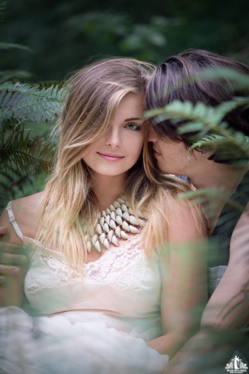 Natural light portrait of a young couple cuddling, the young woman smiling at the camera