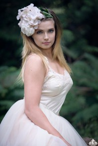 Portrait of a young woman with a flower crown posing in wooded area