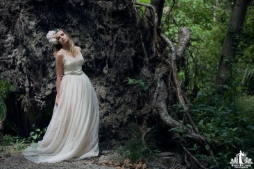 Natural light portrait of a young woman with a flower crown and tulle and lace dress posing in a wooded area