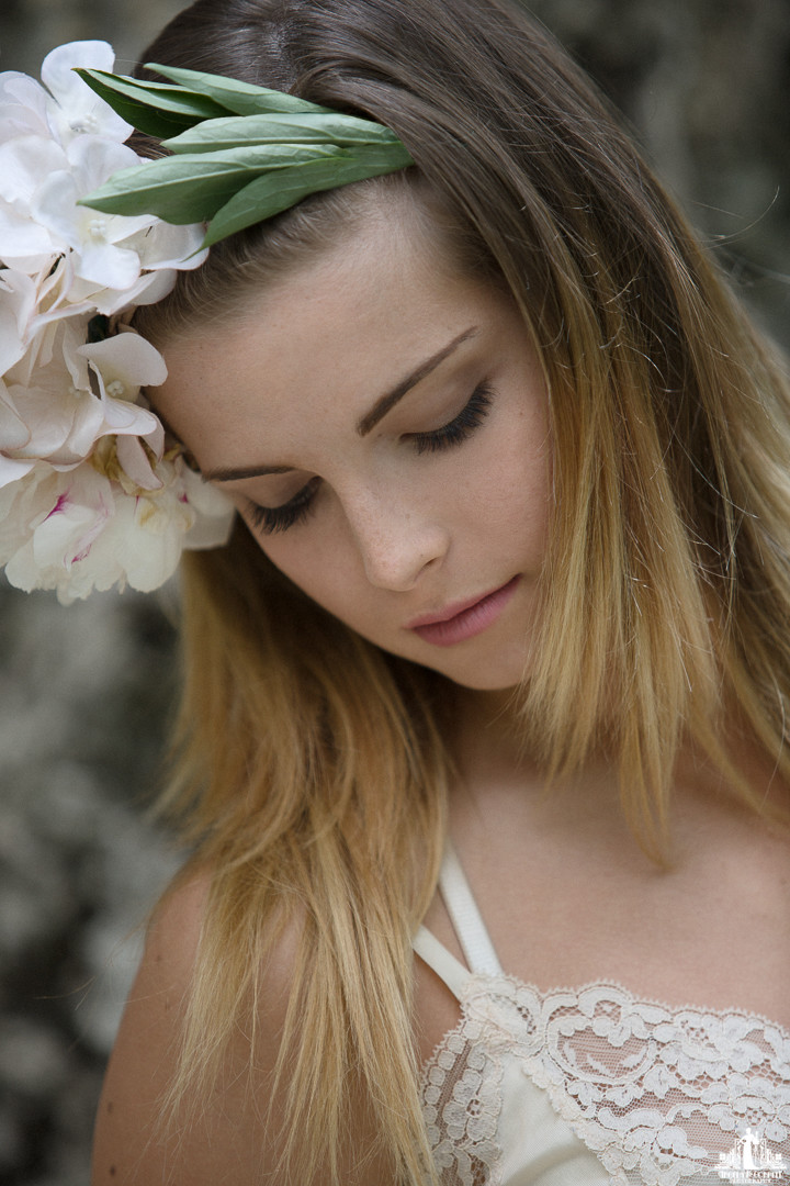 Natural light portrait of a young woman with a flower crown looking down
