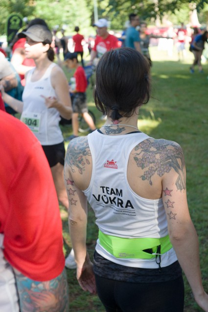 Tattooed woman wearing a Team VOKRA tank top stretching before a run
