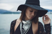 Natural light portrait of a young woman in a black hat and wearing stacked silver necklaces looking down with English Bay in the background