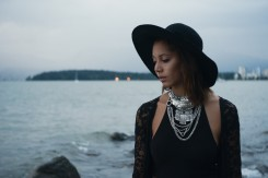 Natural light portrait of a young woman in a black hat and silver necklaces with English Bay and Stanley Park in the distance