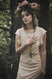 Natural light portrait of a young woman wearing a flower crown standing in front of a tree trunk with her hand on her heart