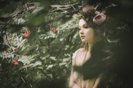 Natural light portrait of a young woman wearing a flower crown framed by leaves in a wooded area