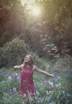 Natural light image of a young woman with outstretched arms in a field of wildflowers backlit by the setting sun