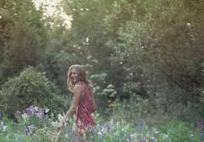 Natural light portrait of a young woman laughing in a field of wildflowers