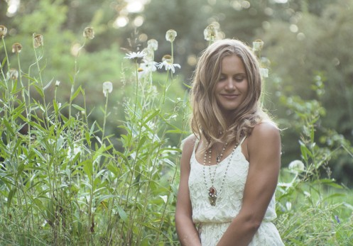 Natural light portrait of a young woman surrounded by daisies