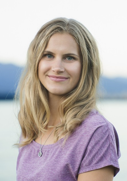 Natural light head shot of a young woman with mountain ranges and water in the background