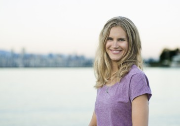 Natural light head shot of a young woman with the Vancouver skyline in the background