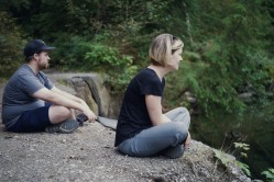 Image of a man and woman sitting looking over a river