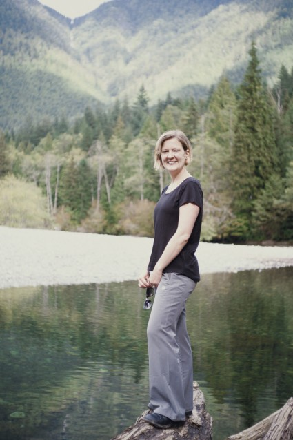 Image of a young woman posing on a log in front of a river and mountain ranges