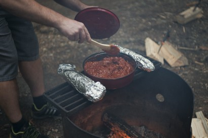 Spaghetti being stirred while warming over a campfire