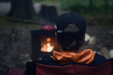 Image of a man sitting in front of a campfire