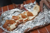 Image of cheesy garlic bread being cut up on tinfoil