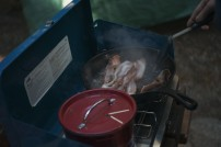 Bacon being grilled on a camp stove