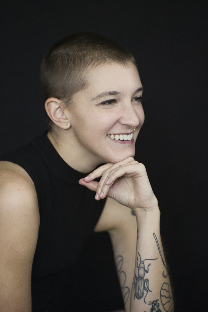 Natural light portrait of a young woman with a shaved head and tattoos resting her chin on her hand and smiling