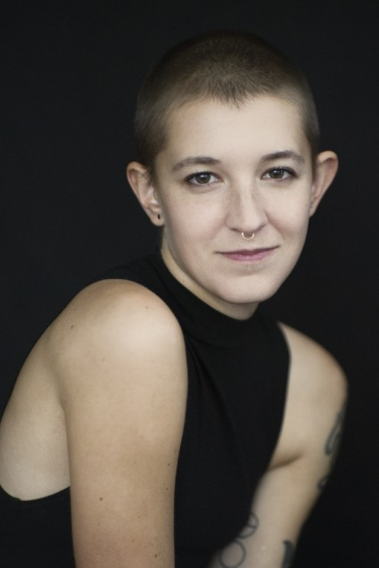 Natural light portrait of a young woman with a shaved head smiling at the camera