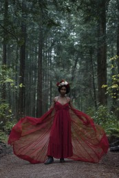 Natural light portrait of a young woman wearing a red dress and a flower crown with chiffon billowing around her standing amongst the trees at Pacific Spirit National Park