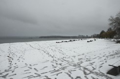 The view from Kitsilano Beach with footprints crossing the snow across to Stanley Park and West Vancouver on a snowy day in Vancouver BC