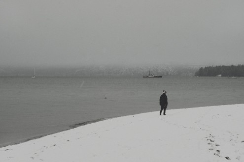 Person walking along Kitsilano Beach with West Vancouver and Stanley Park in the background on a snowy day in Vancouver BC