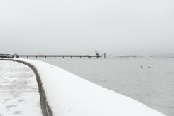 Looking from Kitsilano Beach Pool to the pier at the Kitsilano Yacht club on a snowy day in Vancouver BC