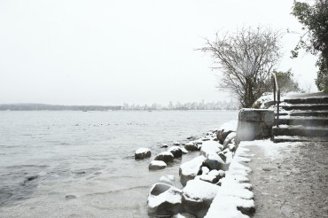 Snow on the footpath and rocks at Point Grey Park looking across to English Bay on a snowy day in Vancouver BC