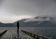 Moody image of a bearded man standing on a pier on Harrison Lake in snow flurries looking across to the snow and cloud covered mountains in the distance